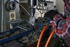 Forant, un homme travaillant à un foret réfrigéré par un liquide Image libre de droits