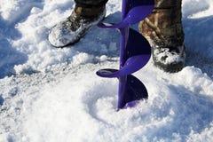 Forant un trou de pêche de glace avec bottes à l'arrière-plan Photographie stock