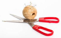 Forbici con le maniglie rosse e una palla dei fili di beige con i perni, Fotografia Stock