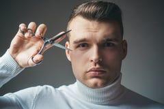 Forbici d'acciaio della tenuta lucida dell'acconciatura del barbiere Crei il vostro stile Capelli sicuri macho del taglio del bar immagini stock
