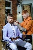 Forbici del barbiere e rasoio diritto Negozio di barbiere di visita del cliente barbuto Balsamo sulle parti del corpo asciutte pe immagini stock libere da diritti