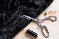 Forbici del sarto che tagliano fine nera della pelliccia Fotografia Stock
