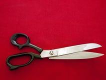 Forbici del sarto di aka di Dressmaking su tessuto rosso Immagine Stock