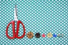 Forbici e bottoni sul fondo del tessuto Fotografie Stock Libere da Diritti