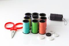 Forbici minuscole e primo piano multicolore del fondo dei filati cucirini Fotografie Stock