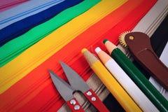 Forbici rosse, matita e taglio rotatorio sulle chiusure lampo variopinte in sei colori differenti Fotografia Stock