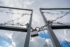 Forbidden area fenced with a barbed wire fence. Gate with padlock closed to the key. Border of States Stock Image
