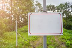 Forbidden area fenced with a barbed wire fence. Gate with padlock closed to the key. Border of States stock photo