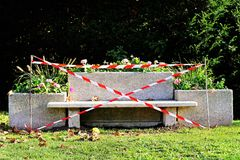 Forbidden bench with red white Caution tape in park. Isolated bench in a city park. There`s no law against sitting on a bench. The lovers kiss on benches stock image