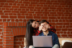 Forbidden content concept. Happy couple with laptop spending time together at home, smiling and having fun. Royalty Free Stock Photos