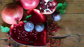 Forbidden fruit. Luscious red pomegranates and purple figs on a heart shaped platter with oregon pine wooden background. Green leaves inbetween Stock Photo