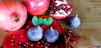Forbidden fruit. Luscious red pomegranates and purple figs on a heart shaped platter with oregon pine wooden background. Green leaves inbetween Stock Photos
