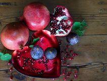 Forbidden fruit. Luscious red pomegranates and purple figs on a heart shaped platter with oregon pine wooden background. Green leaves inbetween Royalty Free Stock Image