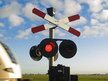 Forbidden to go! Train passing by. Train passing by a railway-crossing with te signal lamp on red Stock Image