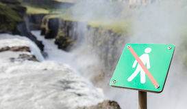Forbidden to walk over here - Iceland - Fierce waterfall in back Royalty Free Stock Photo