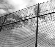 Forbidding fence with razor wire. Wire prison fence topped with razor wire and barbed wire. Monochrome image Stock Photos