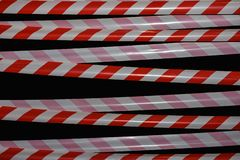Forbidding signal red and white tape on a black background. Forbidding signal red and white tape on black background stock images