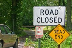 Forbidding Signs. Signs: road closed, dead end, and do not enter, on an overgrown lane with a barrier in the background Royalty Free Stock Photos