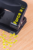 Force a smile concept. Hole punch and extruded paper smiles on the table Royalty Free Stock Photos