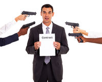 Forced contract. Businessman holding forced contract at gun point Stock Image