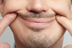 Forced fake smile close up. On male face with beard Royalty Free Stock Images