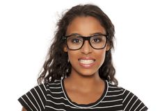 Forced smile. Beautiful young dark skinned woman with eyeglasses  and forced smile on a white background Royalty Free Stock Photo