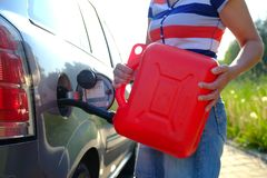 Forced stop. Ran out of gas in the tank of the car. A woman fills the car with gasoline from a spare tank. Canister of 10 liters.  royalty free stock photos
