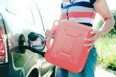 Forced stop. Ran out of gas in the tank of the car. A woman fills the car with gasoline from a spare tank. Canister of 10 liters.  stock image