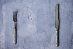Forcella d'annata e coltello su un fondo concreto con spazio libero fotografia stock libera da diritti