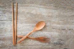 Forcella del cucchiaio ed insieme di legno dell'articolo da cucina dei bastoncini sulla tavola di legno rustica fotografia stock libera da diritti