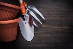 Forcella della cazzuola dei vasi dell'argilla e vanga di giardinaggio della mano su legno d'annata b Fotografie Stock