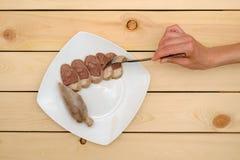 Forcella della tenuta della donna con il pezzo di salsiccia casalinga Immagine Stock