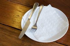 Forcella e coltello con il piatto bianco Fotografie Stock