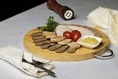 Forcella e coltello in tovagliolo, carne assortita, salsa di formaggio e pomodori ciliegia con gli anelli di cipolla sul tessuto fotografie stock libere da diritti