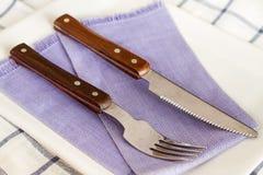 Forcelle e coltelli su un piatto Fotografia Stock Libera da Diritti