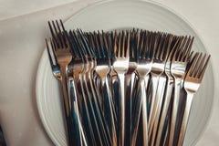 Forcelle pulite pronte per il partito di cena su un piatto, fine su Immagine Stock