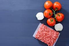 Forcemeat с красными томатами на ветви и отрезанных луках на серой деревянной предпосылке с космосом экземпляра Стоковые Фотографии RF