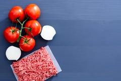 Forcemeat с красными томатами на ветви и отрезанных луках на серой деревянной предпосылке с космосом экземпляра Стоковая Фотография