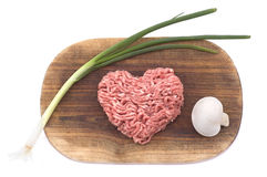 Forcemeat in the form of heart. With a green onions and a champignon on a wooden hardboard isolated on white Stock Image