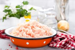 Forcemeat. Raw ground chicken meat in bowl on white kitchen table. Fresh minced chicken breast meat. Selective focus Stock Image