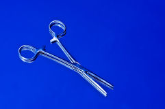 Forceps against blue Royalty Free Stock Photos