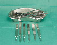 Forceps in kidney shape bowl and scalpel Royalty Free Stock Photo