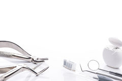 Forceps, toothbrush, dental floss, mouth mirror and dental probe on white background Royalty Free Stock Images