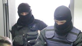 Forces spéciales dans les masques bloquant l'entrée dans l'immeuble de bureaux La police conduit une recherche dans le bureau clips vidéos