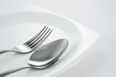 Forchetta & cucchiaio sul piatto bianco Fotografie Stock Libere da Diritti