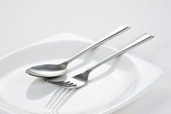 Forchetta & cucchiaio sul piatto bianco Fotografie Stock