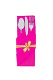 Forchetta, cucchiaio e coltello in panno rosa con l'arco dorato isolato Immagine Stock Libera da Diritti