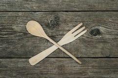 Forchetta e cucchiaio di legno attraversati su fondo rustico Fotografia Stock Libera da Diritti