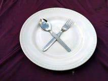 Forchetta e cucchiaio in piatto bianco isolato su un fondo viola fotografia stock