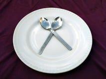 Forchetta e cucchiaio in piatto bianco isolato su un fondo viola fotografie stock